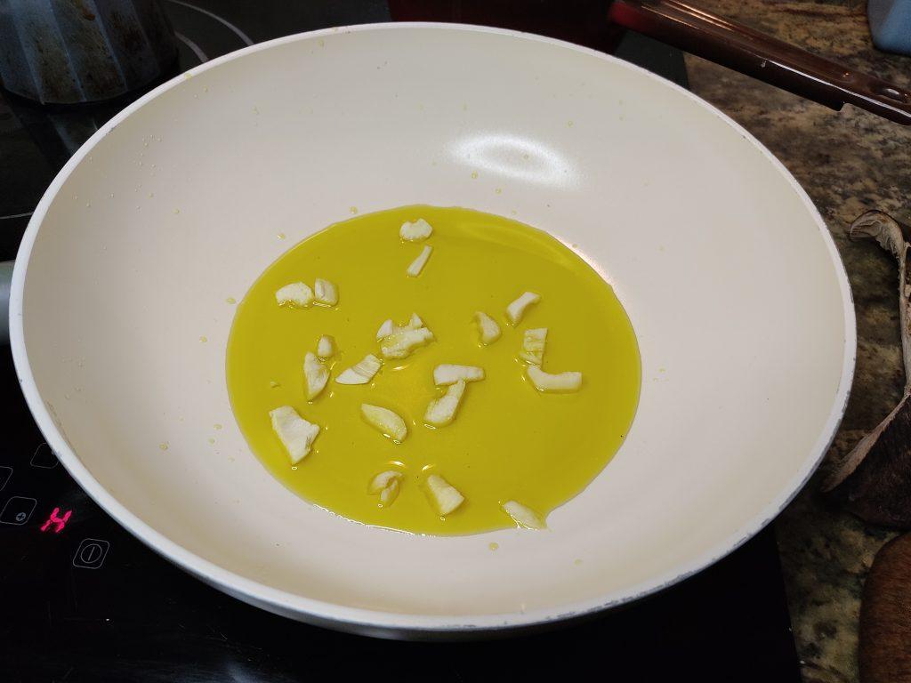 Sartén con aceite de oliva y ajos dorándose